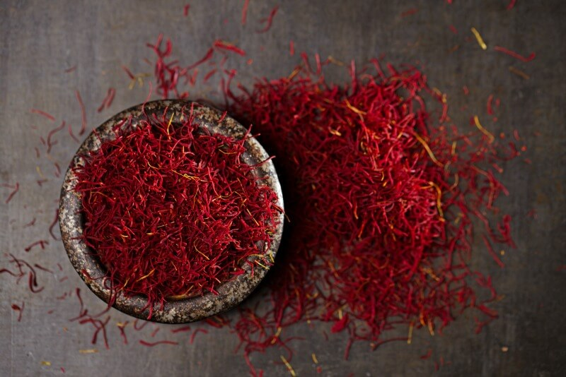 Saffron threads in bowl with pile of saffron threads on the table beside it